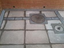 Blue bricks and slabs with manholes and aco drains.
