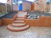 Patio, steps and pathway in bullmose, tumble blocks, and engineering bricks.