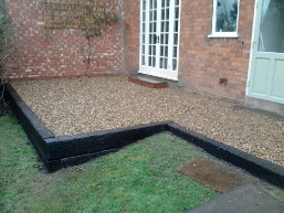 Railway sleeper walls and gravel patio built in rear garden.