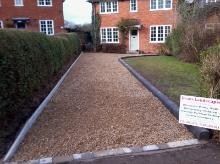Gold gravel driveway with bullnose kerbing and tumble block border.