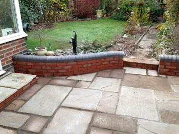 natural stone patio with blue double bullnose topped wall and step